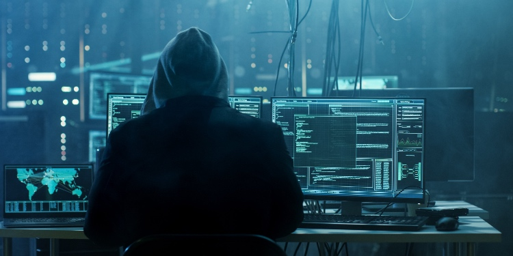 Hacker sits in from of multiple computer screens in a dark room