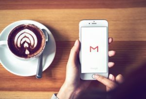 iPhone with Gmail logo displayed and cup of coffee in the background